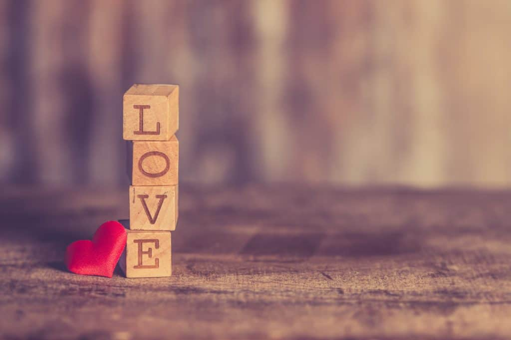 A photo of a heart and wooden blocks that spell out LOVE