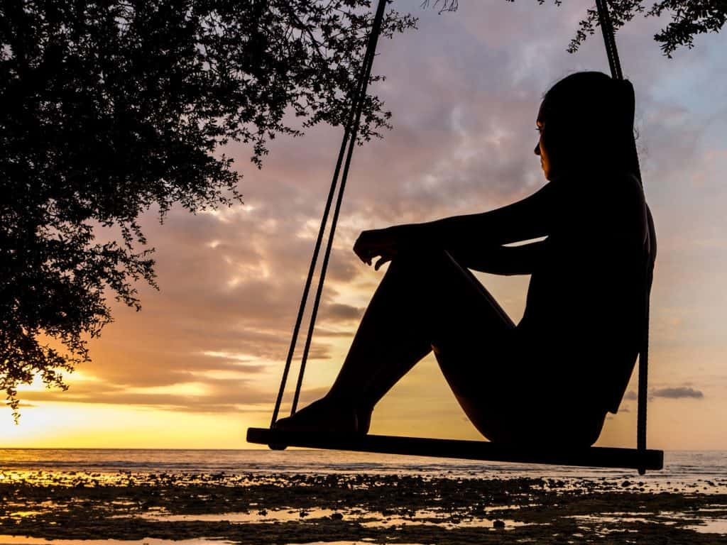 A photo of a woman sitting on a swing watching the sunset observing her inner voice.