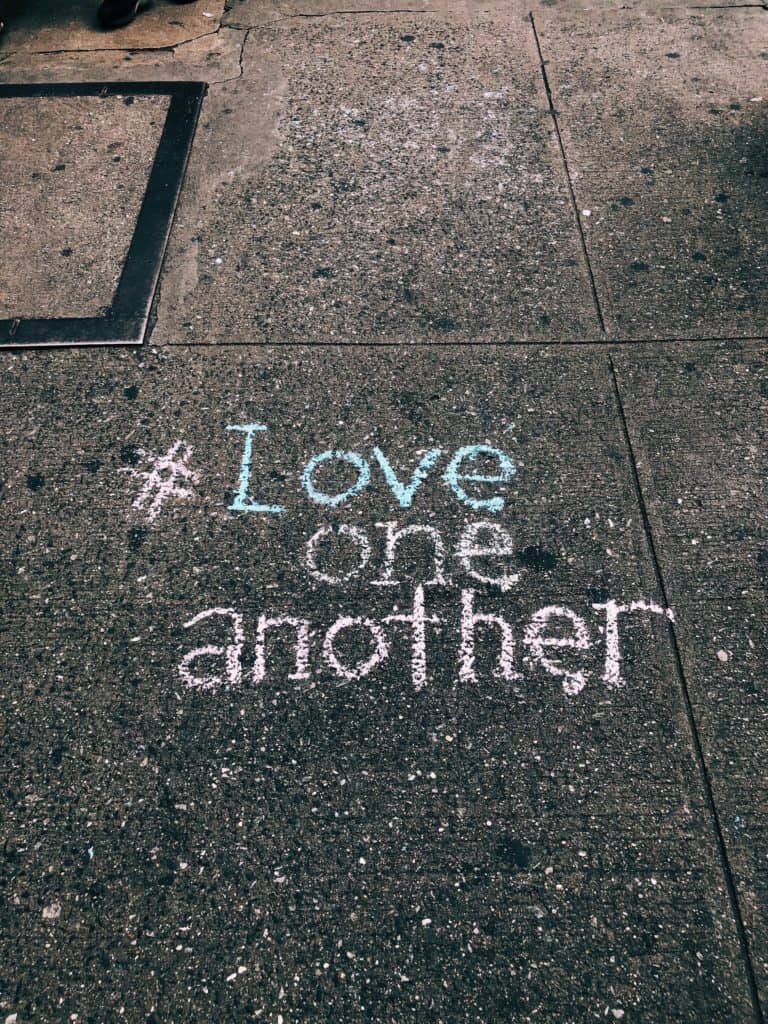 """A photo of a sidewalk with the words written in sidewalk chalk """"#Love one another"""""""