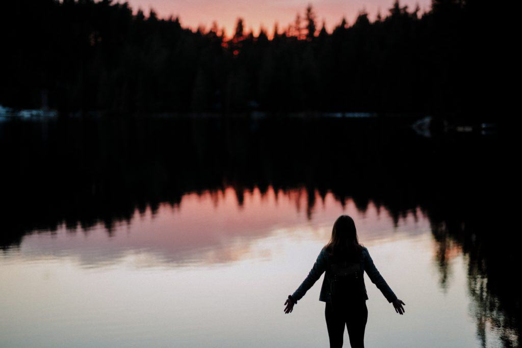A photo of a silhouette of a woman standing by a lake with her arms spread surrendering to the moment.