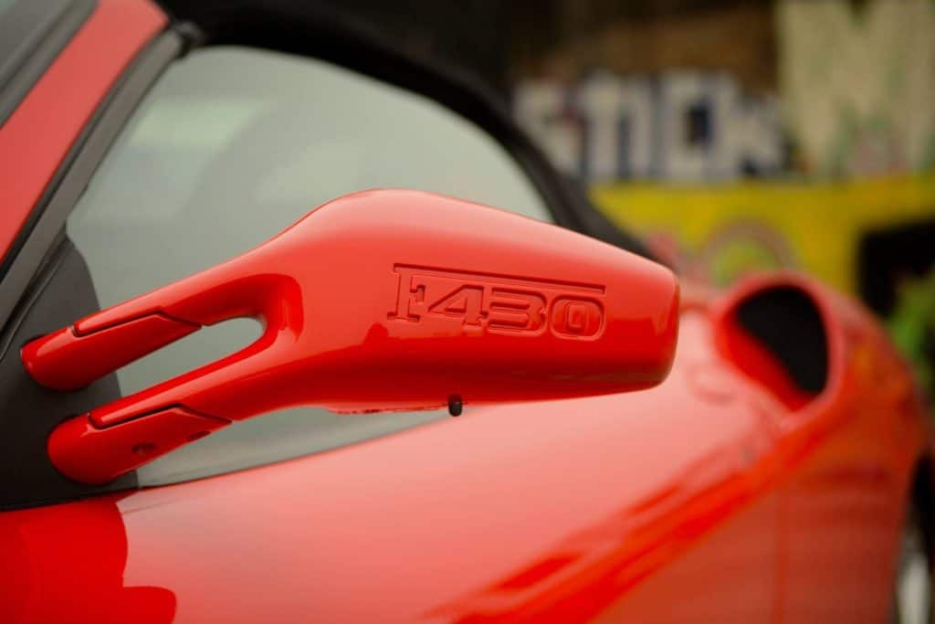 A photo of the back of the side view mirror of a red Ferrari F430.