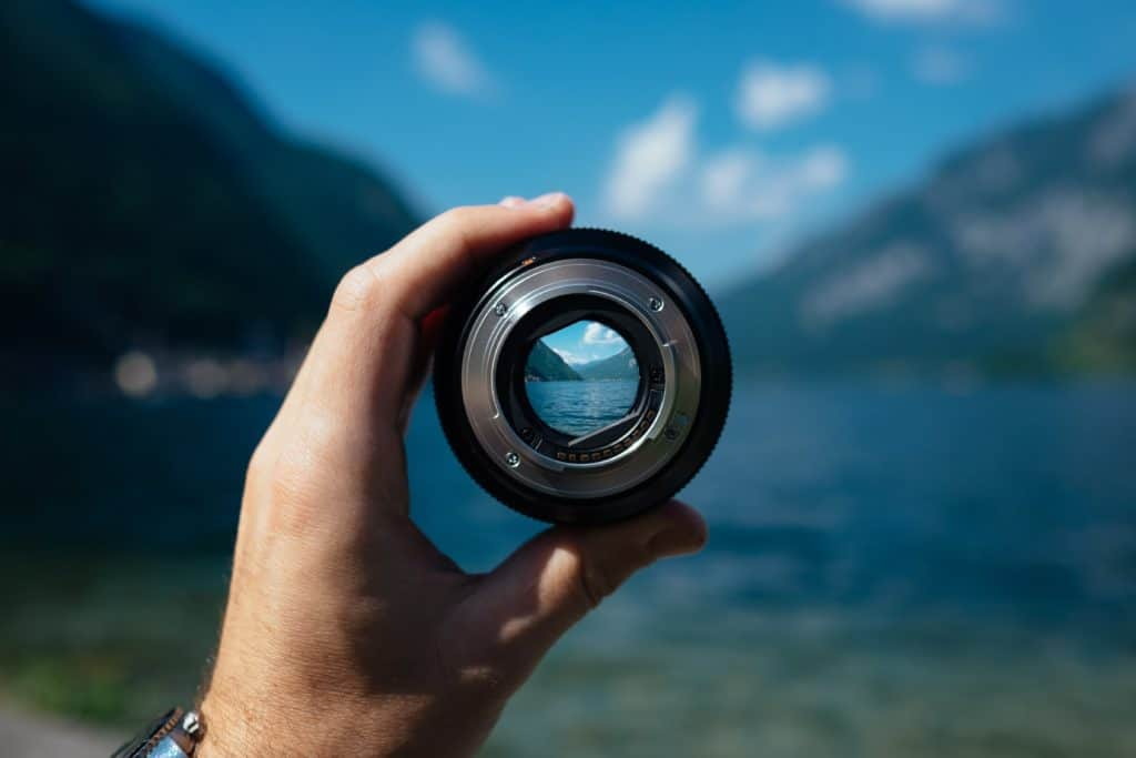 A photo of a camera lens showing the focus through it with the mountain background blurry.