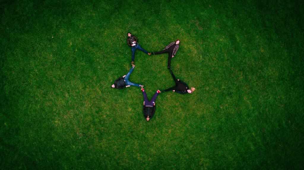A photo of 5 people laying on the ground forming the shape of a star.