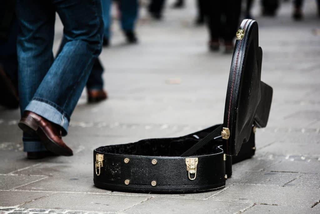A photo of a man walking by a guitar case where people can donate money.