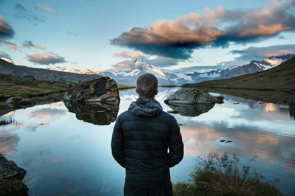 A photo of a man looking over a lake finding peace with Self love.