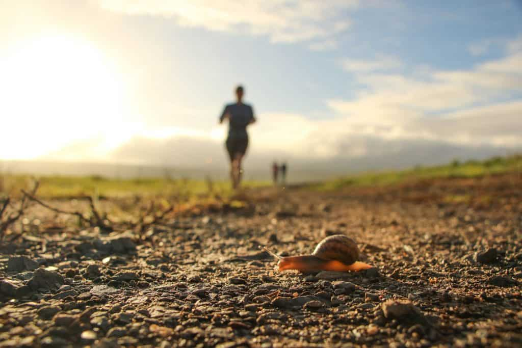 A photo of a man running with a snail on the ground.