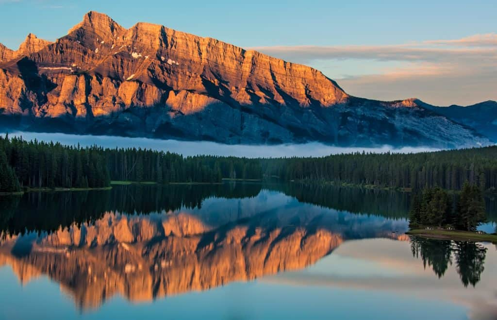 An image of a lake reflecting a mountain.