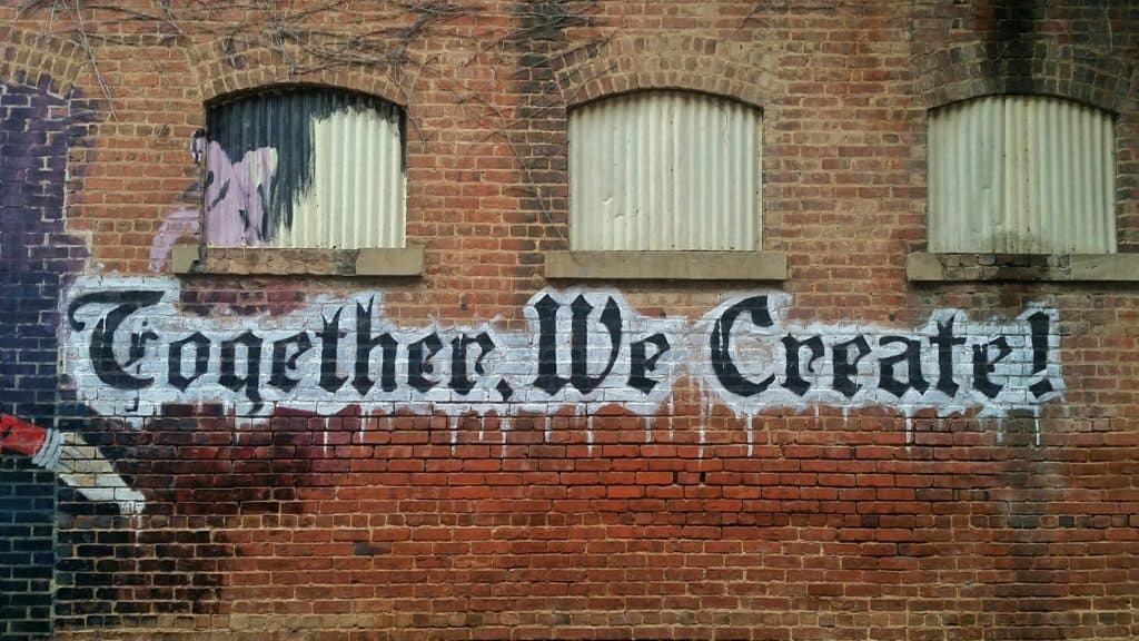 "A photo of a brick wall with graffiti on it that says ""Together we create"""