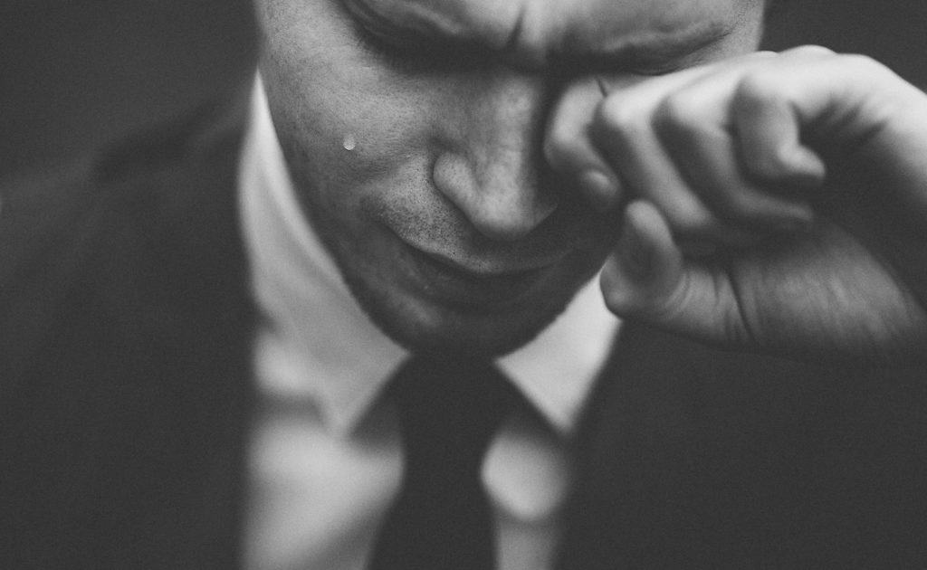 An image of a man wiping his tears.