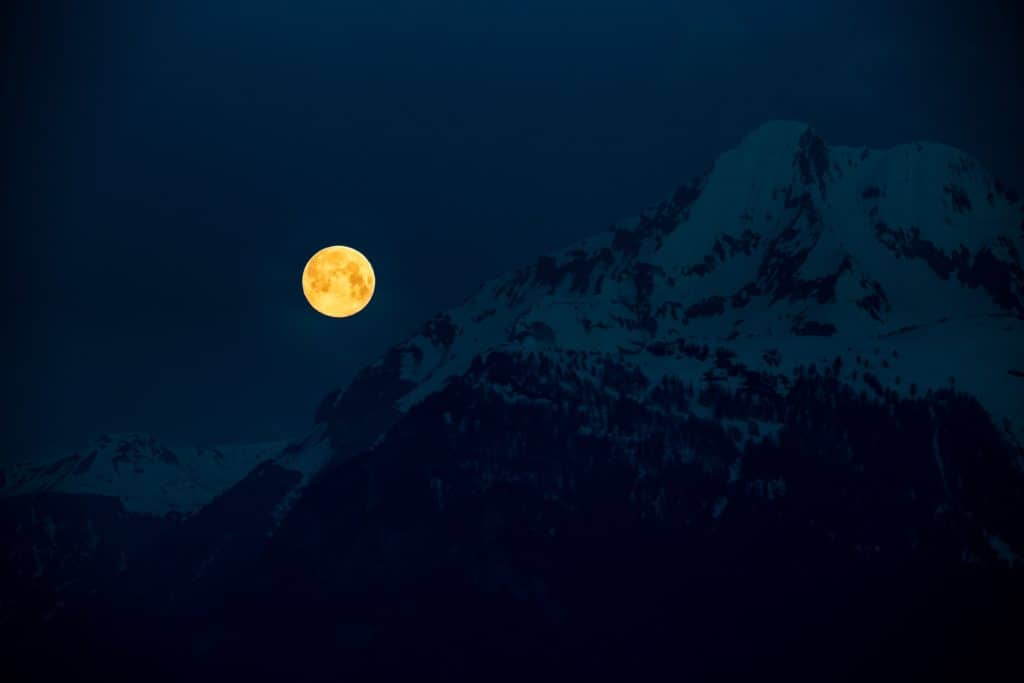 A photo of a full moon rising over a snowy mountain.