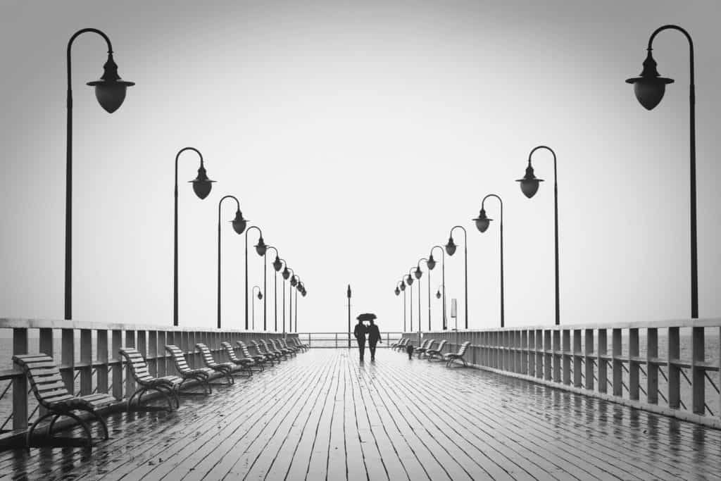 A photo of two people walking in the rain under an umbrella being together as one.