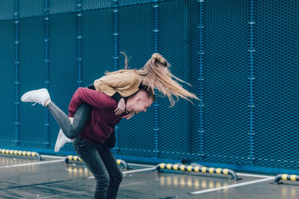 An image of a girl playfully jumping on a guys back.