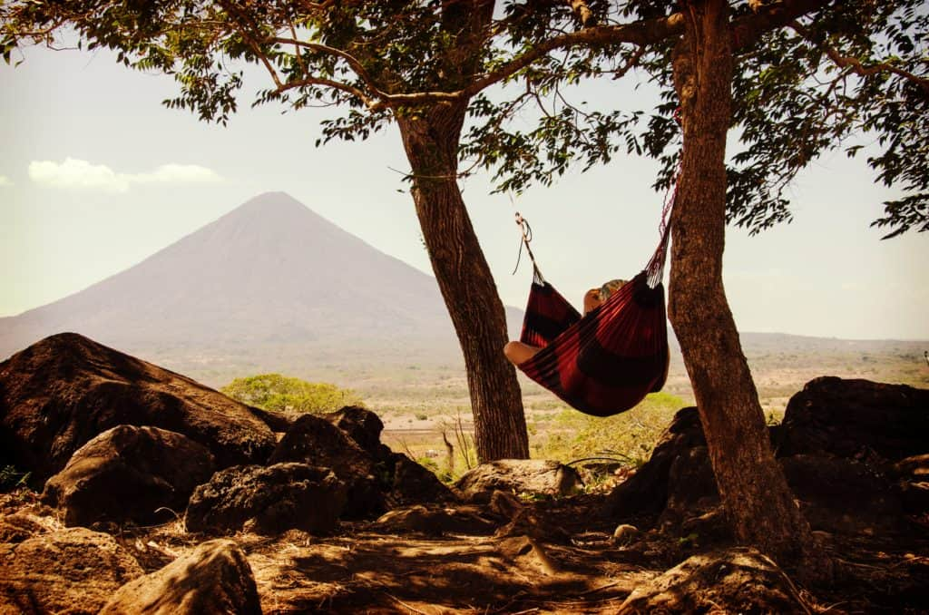 A photo of a person in a hammock relaxing.
