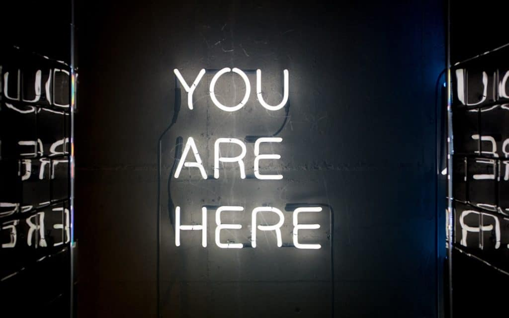 """A picture of a neon sign that says """"You Are Here"""""""