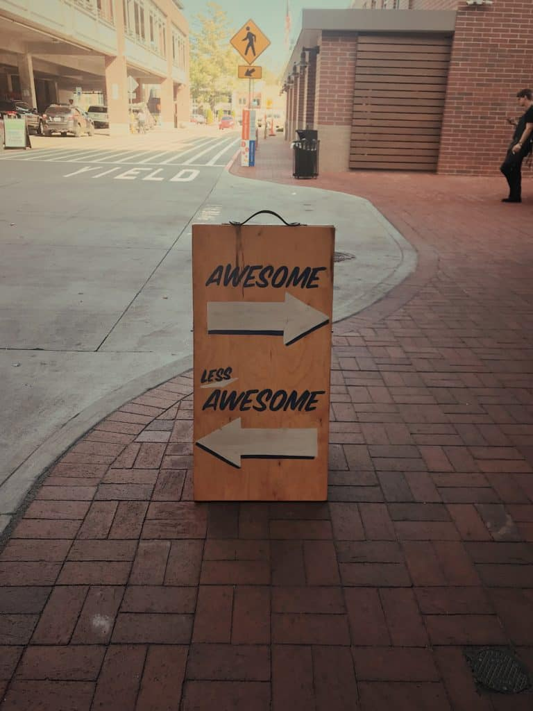 "A photo of a sign with an arrow that says ""Awesome"" pointing to the right and an arrow below that says ""Less Awesome"" pointing to the left."