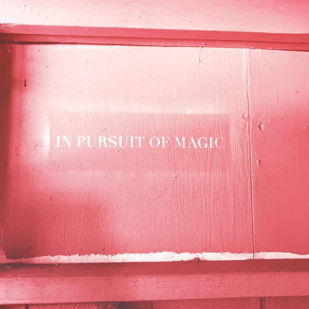"""An image of a pink wall with the words """"In pursuit of magic"""" written on them"""