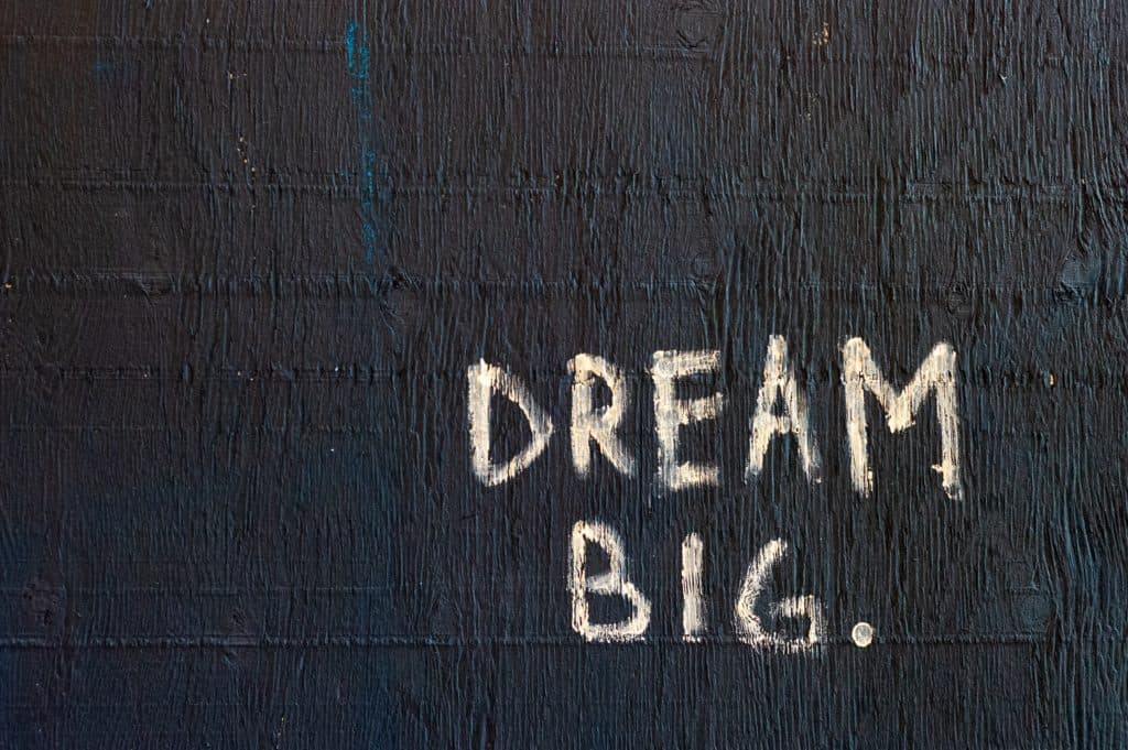 """An image of a painted black wall with the words """"Dream Big"""" written on them."""