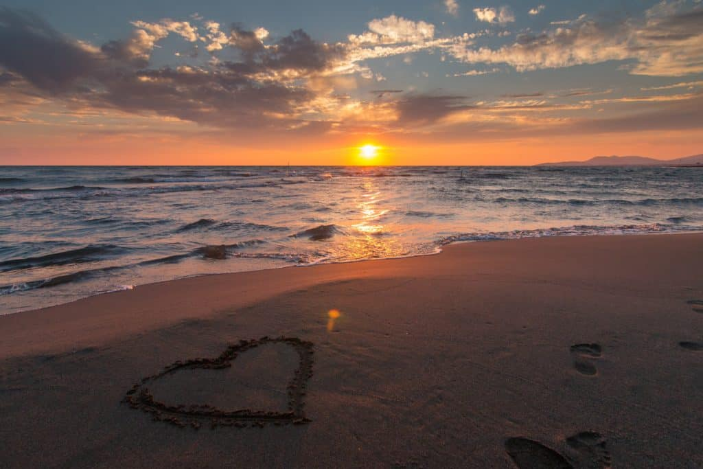 A photo of a heart in the sand with a sunset in the background