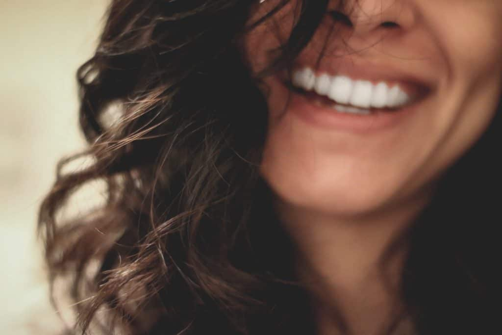 An image of a woman's mouth smiling.
