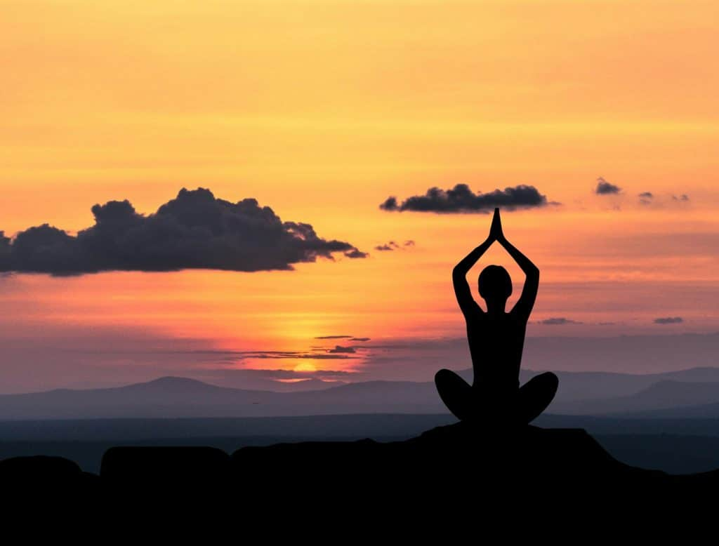 An image of a silhouette sitting in a yoga pose overlooking the sunrise on elevated land.