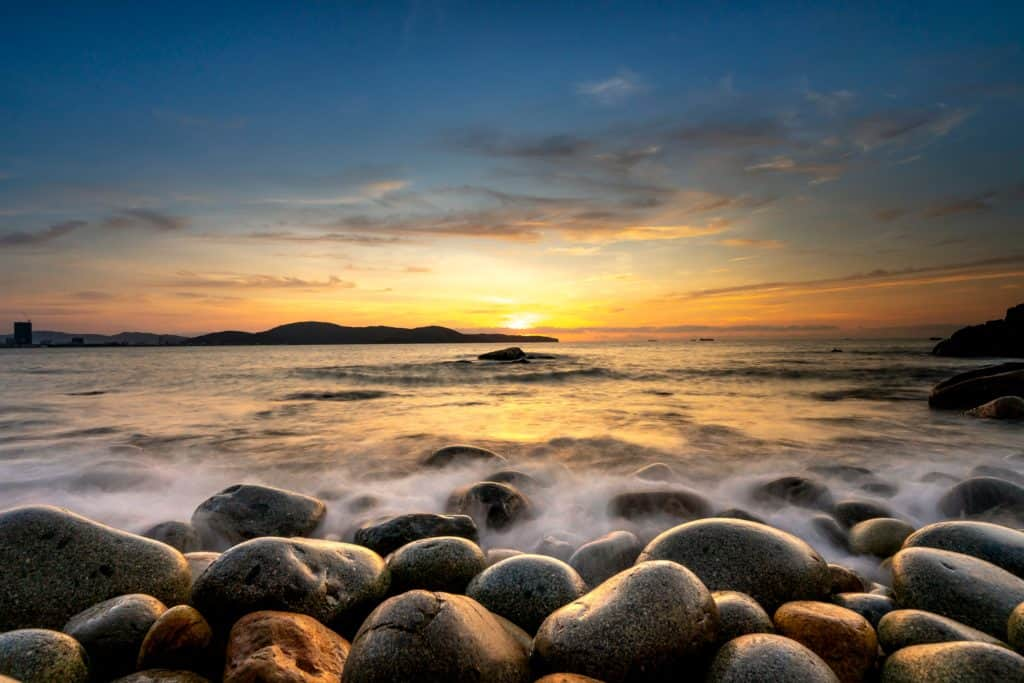 An image of water rolling peacefully over rocks with a sunset in the background