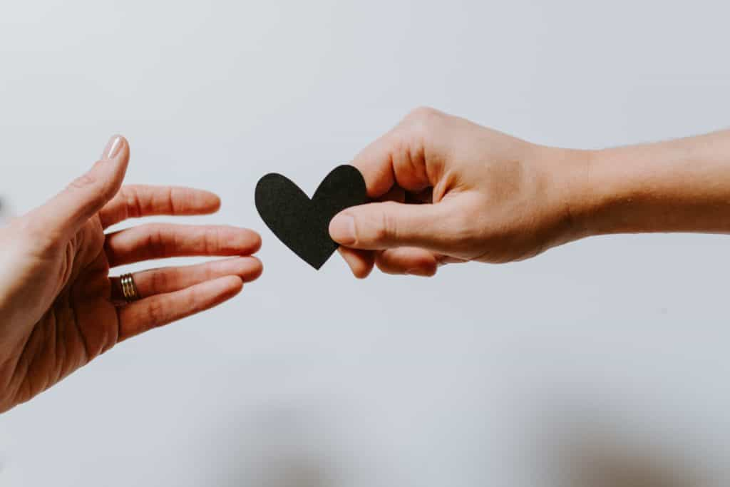An image of two hands giving each other a heart.