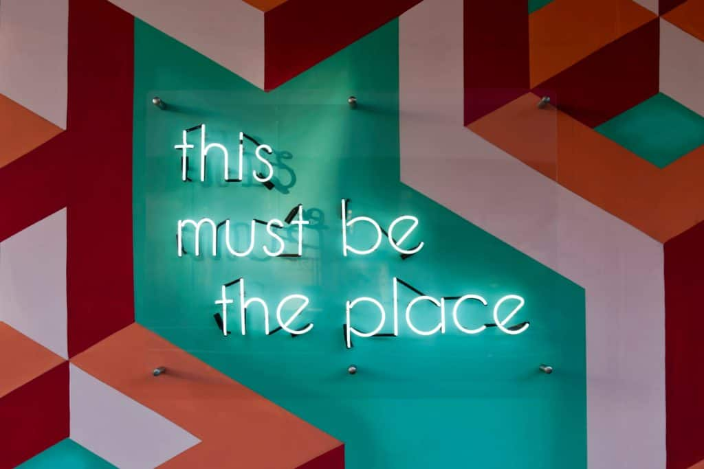 """An image of a Happy painted wall, saying """"This much be the place"""""""