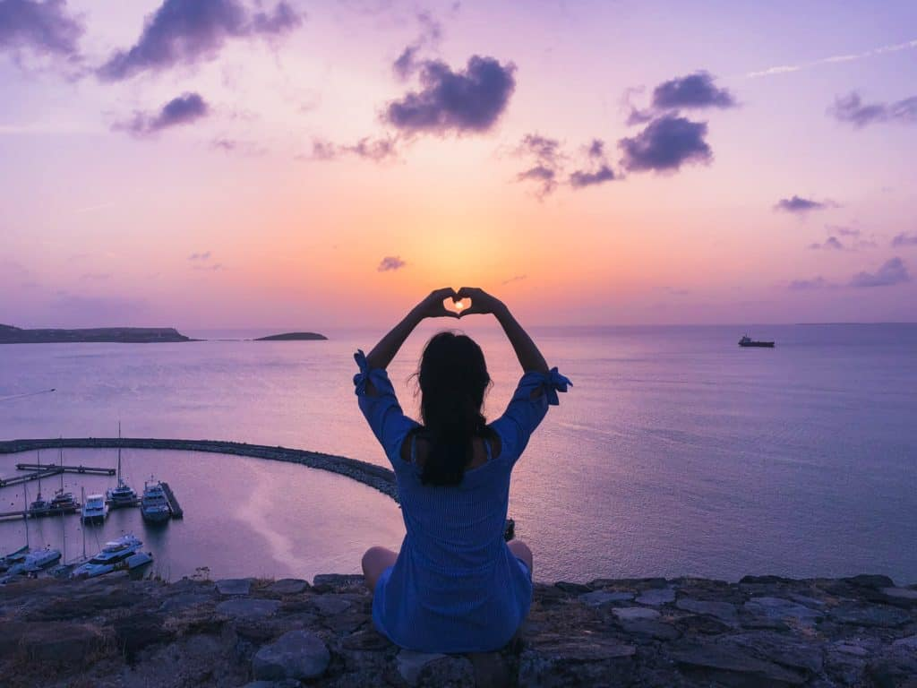 An image of a lady watching a sunset with her hands in the shape of a heart.
