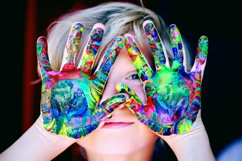 An image of a young child with colorful paint on his hands and they are covering his face.