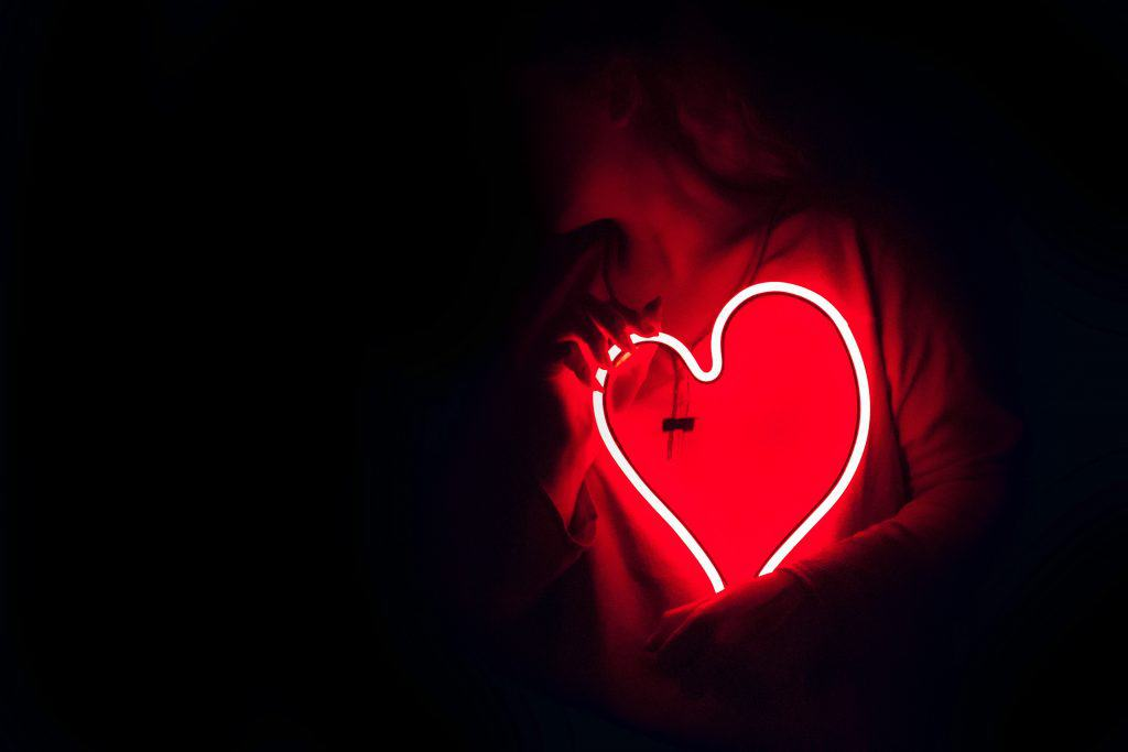 An Image of a person holding a neon lighted heart.
