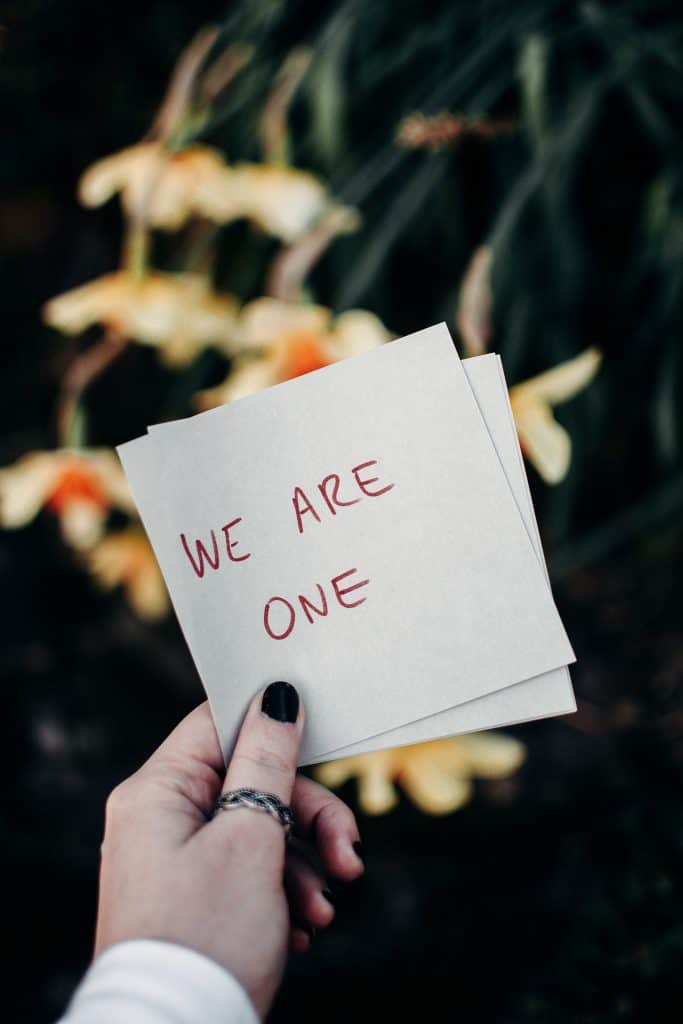 """An image of a hand holding a piece of paper that says """"We are one"""""""