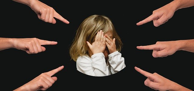 An image of a young girl with many fingers being pointed at her.