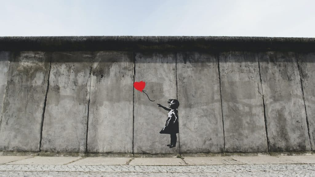 An image of a mural of a small child letting go of a heart shaped balloon.