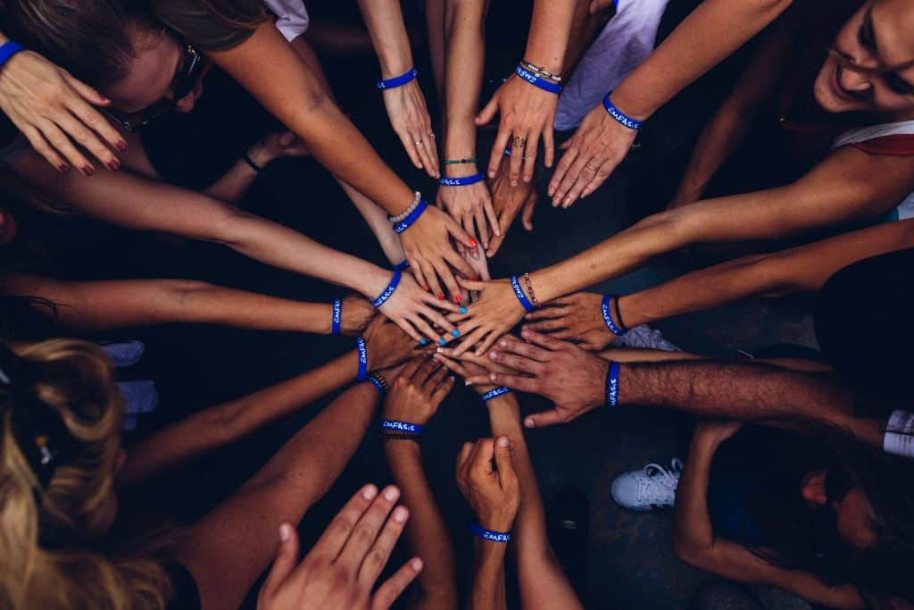 A circle of multiple hands connecting.