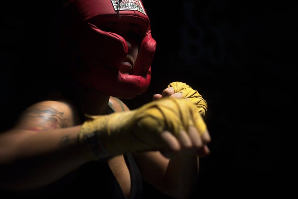 An image of a woman wearing boxing gear ready to fight.