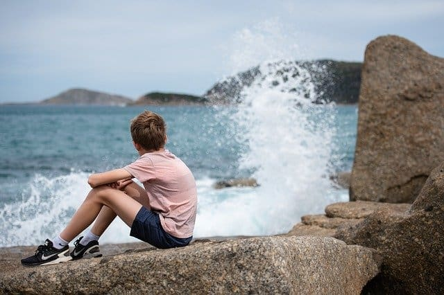 An image of a young man sitting on rocks next to the water thinking.
