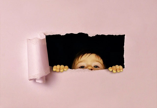An image of a small child peeking through a hole.