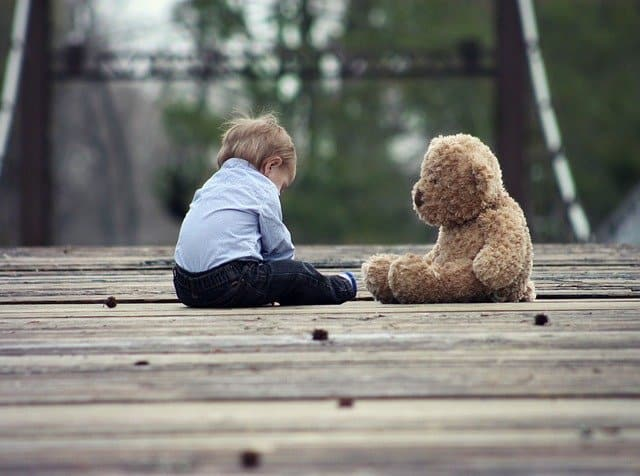 An image of a child sitting with his teddy bear.