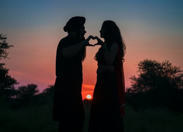 An Image of a couple in love holding up their hands in the shape of a heart.