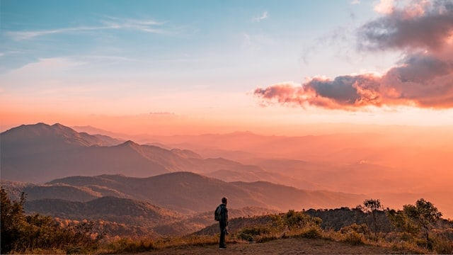 An image of a person standing at sunrise overlooking a mountainous terrain.