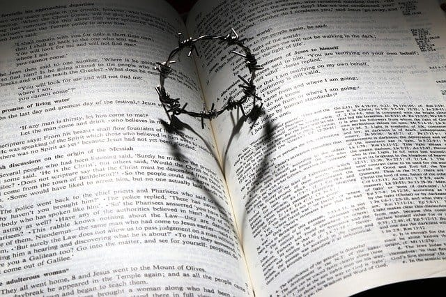 An image of the bible with a crown of thorns that makes the shadow of a heart.