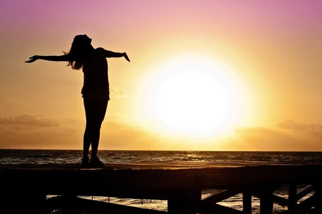 An image of a woman releasing her negative energy as the sunsets.