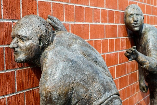 An image of statues listening to a brick wall.