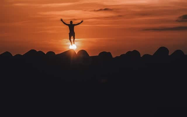 Image of a man's silhouette jumping into a fiery sky.