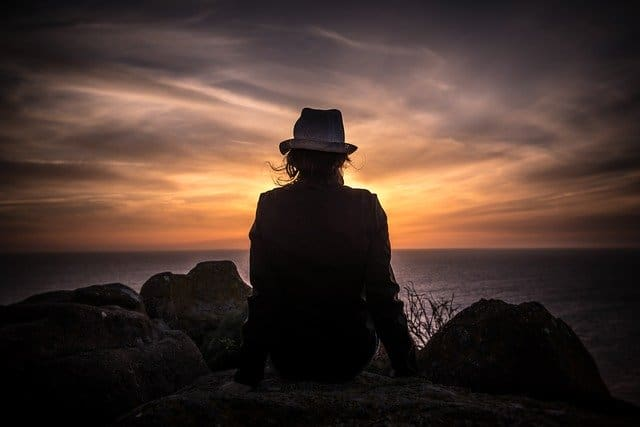 An image of a person wearing a hat watching the sunset.