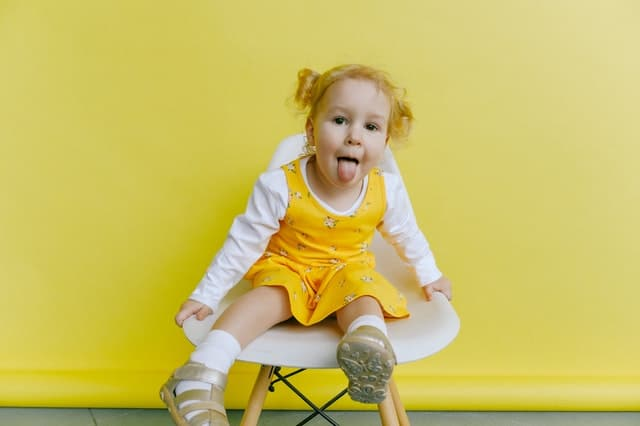 A photo of a toddler girl with her tongue sticking out,