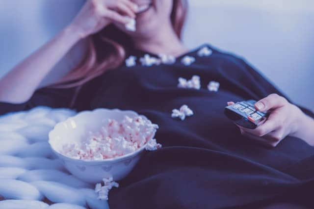 An image of a woman eating popcorn watching a movie.