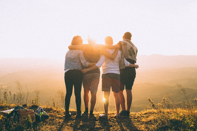 An image of 4 people sharing a hug overlooking a valley.  All Photos by Helena Lopes from Pexels