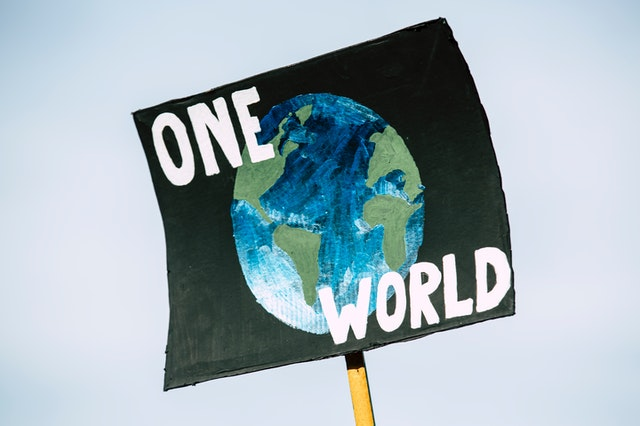 "An image of a sign that has a world on it and says the words ""One World""  Photo by Markus Spiske from Pexels"