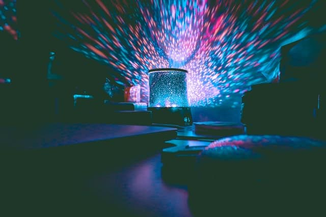 An image of disco lights in a dark room.  Photo by Hasan Albari from Pexels